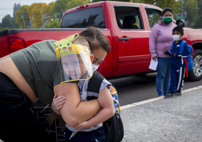FILE - In this Sept. 21, 2020, file photo, Vanessa Mendez hugs her son, Evan Seppa, as he prepares to head into Elizabeth Page Elementary School for his first day of kindergarten in Springfield, Ore. Even as the federal Centers for Disease Control and Prevention moved earlier this month to ease indoor mask-wearing guidance for fully vaccinated people, states like Oregon and Washington are still holding on to certain longtime coronavirus restrictions. (Andy Nelson/The Register-Guard via AP, File)
