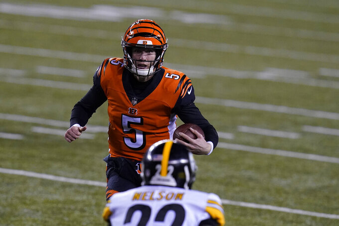 Cincinnati Bengals quarterback Ryan Finley (5) runs against Pittsburgh Steelers' Steven Nelson (22) during the first half of an NFL football game, Monday, Dec. 21, 2020, in Cincinnati. (AP Photo/Michael Conroy)