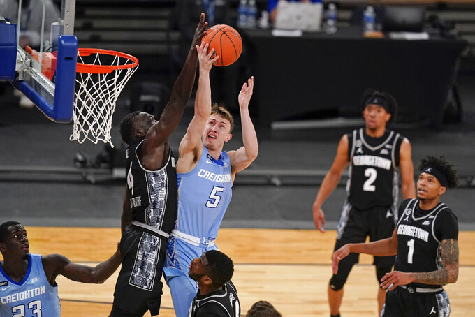 Georgetown's Chudier Bile (4) blocks a shot by Creighton's Alex O'Connell (5) during the second half of an NCAA college basketball game in the championship of the Big East Conference tournament Saturday, March 13, 2021, in New York. (AP Photo/Frank Franklin II)