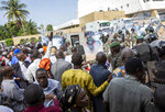Security forces fire tear gas at people gathered outside a conference to discuss a transition to a civilian government in Bamako, Mali, Thursday, Sept. 10, 2020. Leaders of Mali's military junta who deposed the West African country's president last month are meeting with political parties and civil society groups to outline a transition to a civilian government and, ultimately, elections. (AP Photo)