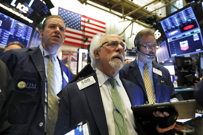 Peter Tuchman, center, works with fellow traders on the floor of the New York Stock Exchange, Wednesday, June 19, 2019. Investors are in wait-and-see mode hours ahead of a widely anticipated Federal Reserve decision on interest rates. (AP Photo/Richard Drew)