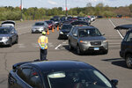 FILE- In this May 7, 2020 file photo, cars line up at a Foodshare distribution center at Rentschler Field in East Hartford, Conn., during the coronavirus pandemic. Officials at the regional food bank have seen an increase in the number of cars arriving at food pick-up locations, such as Rentschler Field in East Hartford, as the extra federal unemployment benefits expire. (AP Photo/Mark Lennihan)