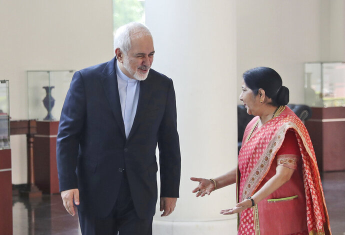Indian Foreign Minister Sushma Swaraj, right, talks with her Iranian counterpart Mohammad Javad Zarif in New Delhi, India, Tuesday, May 14, 2019. Zarif's visit to New Delhi comes within days of the United States ending its waiver to India that allowed it to buy Iranian oil without facing American sanctions. (AP Photo/Manish Swarup)