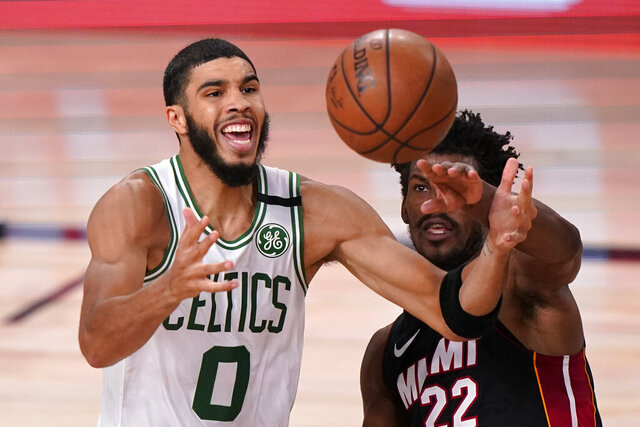 Boston Celtics' Jayson Tatum (0) and Miami Heat's Jimmy Butler (22) battle for a rebound during the second half of an NBA conference final playoff basketball game Sunday, Sept. 27, 2020, in Lake Buena Vista, Fla. (AP Photo/Mark J. Terrill)