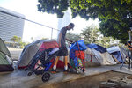 A homeless man moves his belongings from a street behind Los Angeles City Hall as crews prepared to clean the area Monday, July 1, 2019. Los Angeles Mayor Eric Garcetti and a group of other city leaders from around California and the nation are backing the proposed Ending Homelessness Act. The legislation sponsored by U.S. Rep. Maxine Waters, D-Calif., would use more than $13 billion to the efforts of cities to deal with the homelessness crisis. (AP Photo/Richard Vogel)