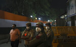 In this Sunday, Nov. 3, 2019, photo, policemen wear pollution masks and guard outside a cricket stadium in New Delhi, India. Authorities in New Delhi are restricting the use of private vehicles on the roads under an