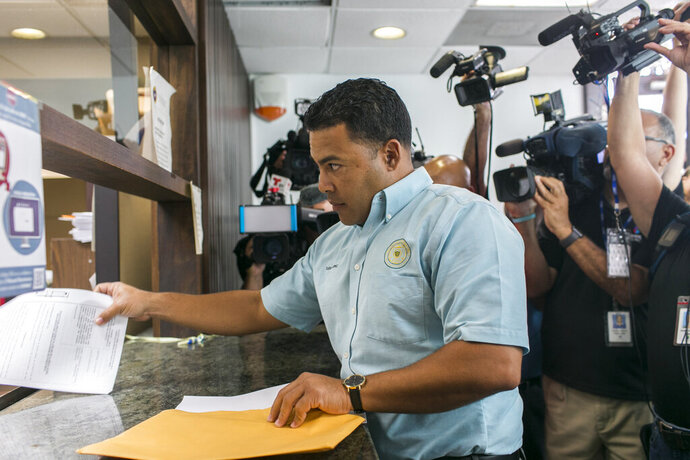A messenger representing the Inter American University of Puerto Rico Law School files paperwork regarding Pedro Pierluisi, recently sworn in as the island's governor, in San Juan, Puerto Rico, Tuesday, Aug. 6, 2019. Attorneys submitted arguments by a Tuesday noon deadline in what many consider the biggest decision in the 119-year history of Puerto Rico's Supreme Court: who will be the governor of the U.S. territory mired in political and economic turmoil. (AP Photo/Dennis M. Rivera Pichardo)