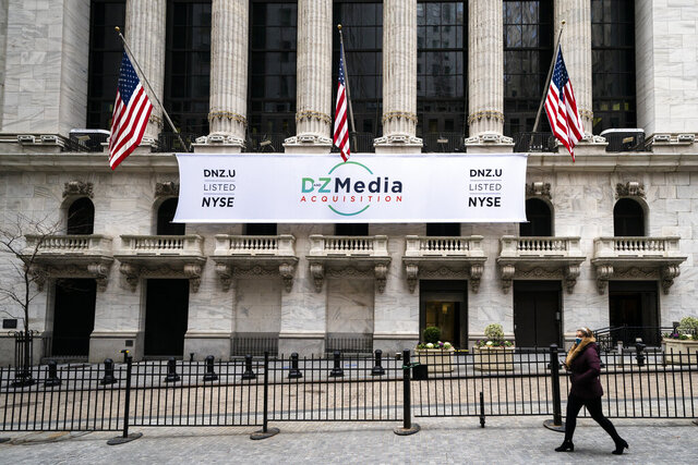 Pedestrians pass the New York Stock Exchange, Wednesday, Jan. 27, 2021, in New York.  Stocks are climbing back in the early going on Wall Street Thursday, a day after the market took its biggest one-day loss since October.  (AP Photo/John Minchillo)