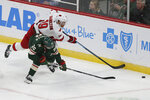 Carolina Hurricanes' Dougie Hamilton reaches for the puck over Minnesota Wild's Mats Zuccarello in the first period of an NHL hockey game Saturday, Nov. 16, 2019, in St. Paul, Minn. (AP Photo/Stacy Bengs)