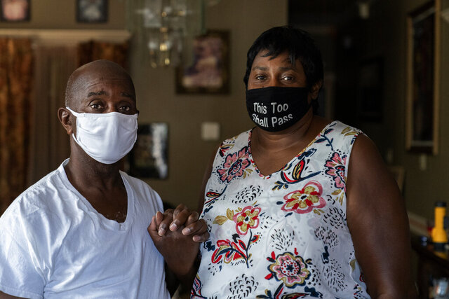 Mary and Barrett Duplessis pose for a portrait in their home in New Orleans, Wednesday, Aug. 19, 2020. Levee breaches following Hurricane Katrina dumped 6 feet of water into the home of Mary Duplessis and her husband in 2005. She remembers lots of paperwork and bureaucracy in her Katrina recovery, and she recalls the scenes of misery at a convention center where thousand were trapped without power or running water. But, for her, COVID-19, has been worse. (AP Photo/Gerald Herbert)