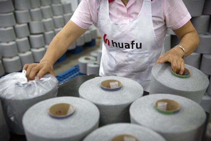 A worker packages spools of cotton yarn at a Huafu Fashion plant, as seen during a government organized trip for foreign journalists, in Aksu in western China's Xinjiang Uyghur Autonomous Region, Tuesday, April 20, 2021. A backlash against reports of forced labor and other abuses of the largely Muslim Uyghur ethnic group in Xinjiang is taking a toll on China's cotton industry, but it's unclear if the pressure will compel the government or companies to change their ways. (AP Photo/Mark Schiefelbein)