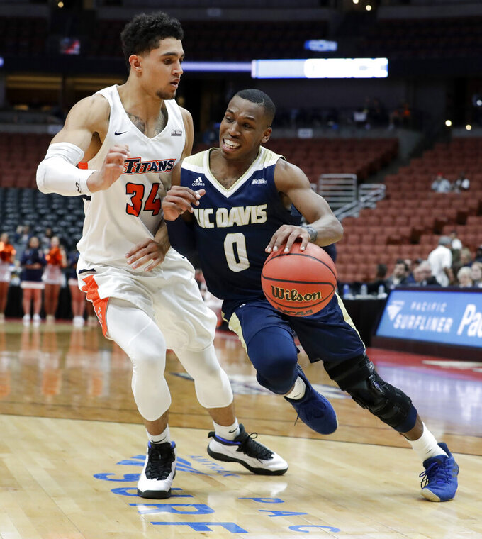 UC Davis guard TJ Shorts II, right, drives around Cal State Fullerton forward Jackson Rowe during the second half of an NCAA college basketball game at the Big West men's tournament in Anaheim, Calif., Thursday, March 14, 2019. (AP Photo/Chris Carlson)