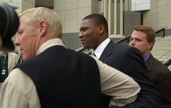FILE - In this Feb. 22, 2000, file photo, Kansas City Chiefs wide receiver Tamarick Vanover, center, is guided towards a waiting car outside the Federal Courthouse in Kansas City, Mo. Former NFL players Clinton Portis, Tamarick Vanover and Robert McCune pleaded guilty for their roles in a nationwide healthcare fraud scheme, the U.S. Department of Justice announced Tuesday, Sept. 7, 2021. (AP Photo/Cliff Schiappa, File)