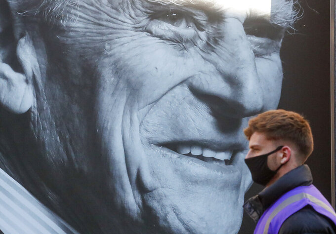 A man walks past a portrait of Britain's Prince Philip ahead of his funeral in Windsor, England Saturday April 17, 2021. Philip died April 9 at the age of 99 after 73 years of marriage to Britain's Queen Elizabeth II. Coronavirus restrictions mean there will be only 30 mourners for the service, including the widowed queen, her four children and her eight grandchildren. (AP Photo/Frank Augstein)