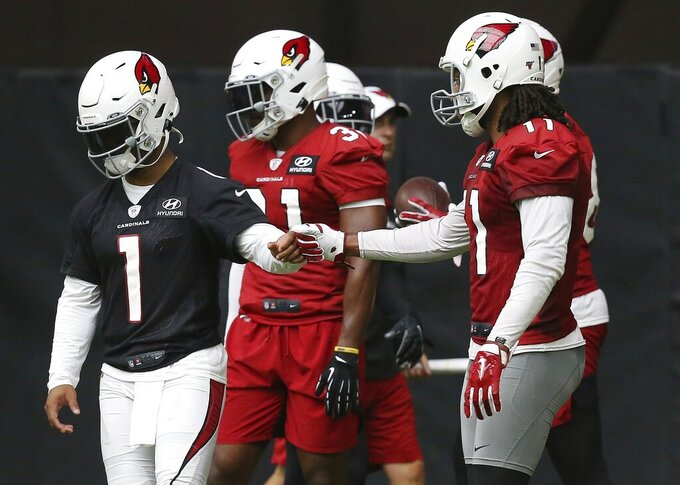 Arizona Cardinals quarterback Kyler Murray (1) gets a fist bump from Cardinals wide receiver Larry Fitzgerald, right, after the two connected on a pass completion during NFL football practice at State Farm Stadium Friday, July 26, 2019, in Glendale, Ariz. (AP Photo/Ross D. Franklin)