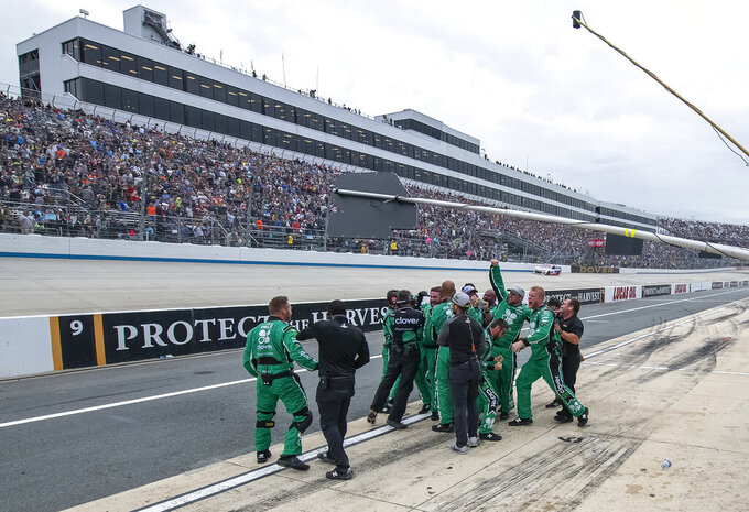 Kyle Larson's team celebrates on pit road after he won the NASCAR Cup Series playoff auto race Sunday, Oct. 6, 2019, at Dover International Speedway in Dover, Del. (AP Photo/Jason Minto)