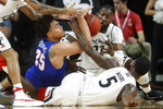 SMU's Ethan Chargois (25), Cincinnati's Trevor Moore (5), and Eliel Nsoseme, top right, battle for a loose ball in the first half of an NCAA college basketball game Saturday, Feb. 2, 2019, in Cincinnati. (AP Photo/John Minchillo)