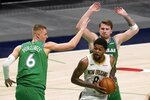 Dallas Mavericks' Kristaps Porzingis (6) and Luka Doncic, rear, defend as New Orleans Pelicans forward Naji Marshall (8) works for a shot during the second half of an NBA basketball game in Dallas, Wednesday, May 12, 2021. (AP Photo/Tony Gutierrez)