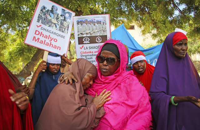 Somali women protest in memory of their relatives who died in Saturday's truck bombing which killed at least 78 people, during a protest to show solidarity with them and against such attacks, in the capital Mogadishu, Somalia, Thursday, Jan, 2, 2020. Placards in Somali read