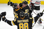 Boston Bruins defenseman Torey Krug (47) celebrates his goal with defenseman Charlie McAvoy (73) and right wing David Pastrnak (88) during the third period of an NHL hockey game against the Chicago Blackhawks, Thursday, Dec. 5, 2019, in Boston. (AP Photo/Elise Amendola)