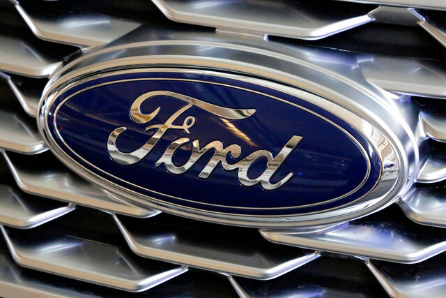 FILE- This Feb. 15, 2018, file photo shows a Ford logo on the grill of a 2018 Ford Explorer on display at the Pittsburgh Auto Show.  Ford Motor Co. will offer early retirement incentives with hopes of cutting its U.S. white-collar workforce by 1,400 more positions. President for the Americas Kumar Galhotra told employees about the offers Wednesday, Sept. 2, 2020.   (AP Photo/Gene J. Puskar, File)