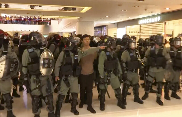 In this image made from video, a protester is arrested by police at a shopping mall in Sha Tin district in Hong Kong, with shoppers watch from balconies above, Sunday, Dec. 15, 2019.  The rally, which had a Christmas shopping theme, was the latest in a series of demonstrations, which have beset Hong Kong for more than six months.(AP Photo)