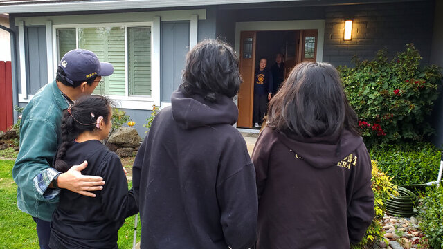 This March 2020 photo provided by Graciela Tiscareño-Sato of Castro Valley, Calif., shows her with her husband and children, foreground, singing to her mother-in-law for her 79th birthday at a safe distance due to the COVID-19 coronavirus outbreak.