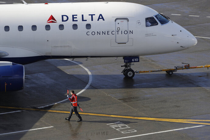 FIE - In this Feb. 5, 2019, file photo a ramp worker guides a Delta Air Lines plane at Seattle-Tacoma International Airport in Seattle. Delta says earnings and revenue will rise in 2020 because of continuing solid demand for air travel and no increase in spending on jet fuel. CEO Ed Bastian says Delta is getting a boost from strong spending by consumers, which he expects to spill into 2020.  (AP Photo/Ted S. Warren, File)