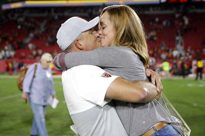 Southern California coach Clay Helton kisses his wife, Angela, after the team's 30-23 win over Utah in an NCAA college football game Friday, Sept. 20, 2019, in Los Angeles. (AP Photo/Marcio Jose Sanchez)