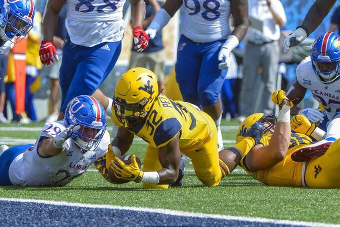 West Virginia running back Martell Pettaway (32) recovers the football after fumbling during the first half of an NCAA college football game against Kansas in Morgantown, W. Va., Saturday Oct. 6, 2018. (AP Photo/Craig Hudson)