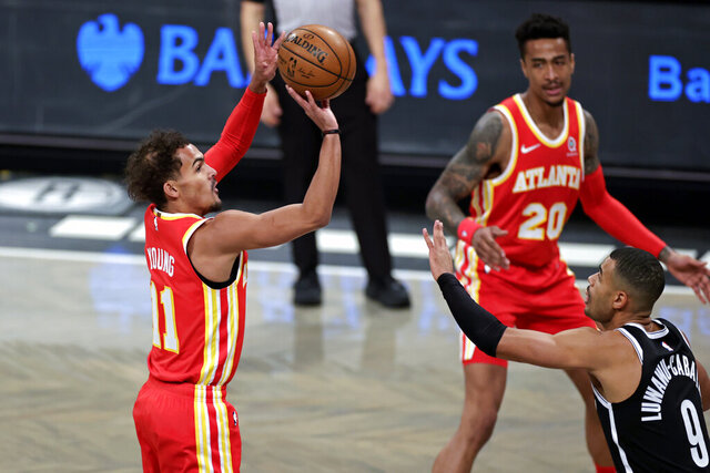 Atlanta Hawks guard Trae Young (11) shoots over Brooklyn Nets guard Timothe Luwawu-Cabarrot (9) during the first half of an NBA basketball game Friday, Jan. 1, 2021, in New York. (AP Photo/Adam Hunger)