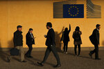 Commuters walk past the European Commission logo outside the EU headquarters in Brussels, Friday, Oct. 25, 2019. European Union ambassadors are meeting in Brussels Friday to discuss what kind of extension to the Brexit deadline they could propose to Britain. (AP Photo/Francisco Seco)