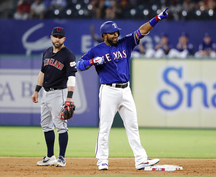 Cleveland Indians second baseman Jason Kipnis, left, looks on as Texas Rangers' Elvis Andrus gestures to the dugout after hitting a run-scoring double in the fifth inning of a baseball game in Arlington, Texas, Monday, June 17, 2019. Shin-Soo Choo scored on the hit. (AP Photo/Tony Gutierrez)