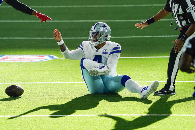 FILE - In this Oct. 11, 2020, file photo, Dallas Cowboys quarterback Dak Prescott motions for medical attention after being injured on a tackle by New York Giants cornerback Logan Ryan during the third quarter of an NFL football game in Arlington, Texas. From the season-altering (Prescott, Saquon Barkley) to the bizarre (Tyrod Taylor, Trent Brown), injuries are playing their traditionally significant role in the NFL. Prescott's Cowboys are on the verge of a lost season because of the players gone for the year. (Smiley N. Pool/The Dallas Morning News via AP, File)