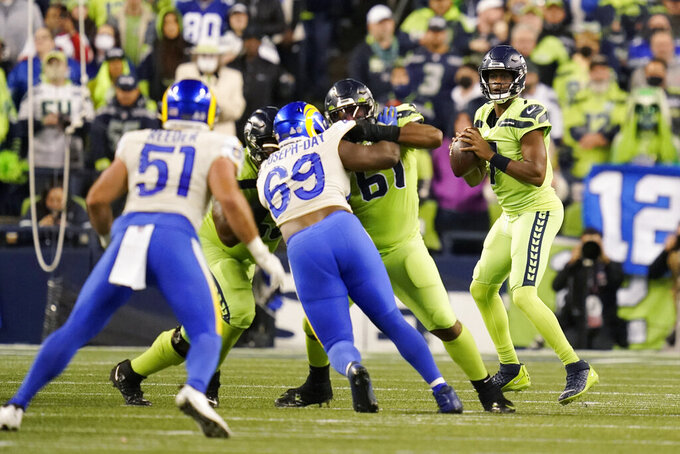 Seattle Seahawks backup quarterback Geno Smith, right, looks to pass against the Los Angeles Rams during the second half of an NFL football game, Thursday, Oct. 7, 2021, in Seattle. (AP Photo/Elaine Thompson)