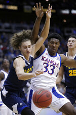 Kansas City forward Josiah Allick, left, and Kansas forward David McCormack (33) battle for a loose ball during the first half of an NCAA college basketball game in Kansas City, Kan., Saturday, Dec. 14, 2019. (AP Photo/Orlin Wagner)
