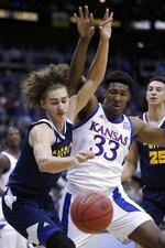 Kansas City forward Josiah Allick, left, and Kansas forward David McCormack (33) battle for a loose ball during the first half of an NCAA college basketball game in Kansas City, Kan., Saturday, Dec. 14, 2019. (AP Photo/Orlin Wagner)