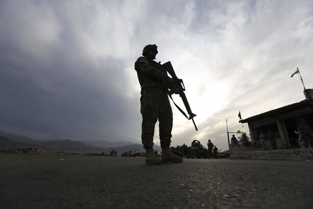 FILE - In this Saturday, April 4, 2020 file photo, an Afghan National Army soldier stands guard at a checkpoint to enforce a curfew for the the fight against the coronavirus, on the Jalalabad-Kabul highway, in the Laghman province, east of Kabul, Afghanistan. (AP Photo/Rahmat Gul, File)