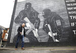 Loyalist activist Jamie Bryson walks past a Ulster Volunteer Force mural in east Belfast, Northern Ireland, Tuesday, Oct. 15, 2019. Fears about a return to the violence that killed more than 3,500 people over three decades have made Northern Ireland the biggest hurdle for U.K. and European Union negotiators trying to hammer out an agreement on Britain's departure from the 28-nation free trade bloc. People here are worried that UK Prime Minister Boris Johnson will sacrifice their interests in hopes of securing a deal. Anything that treats Northern Ireland differently than the rest of the U.K. would be unacceptable.