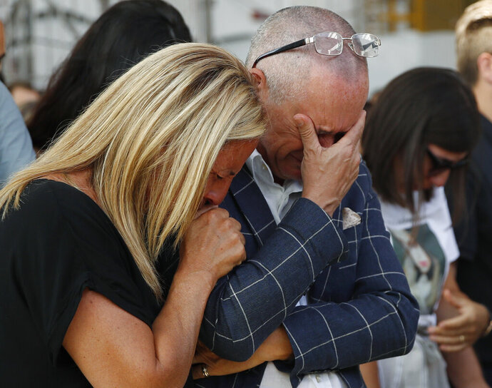 Relatives of the victims of the Morandi bridge collapse, cry during a remembrance ceremony to mark the first anniversary of the tragedy, in Genoa, Italy, Wednesday, Aug. 14, 2019. The Morandi bridge was a road viaduct on the A10 motorway in Genoa, that collapsed one year ago killing 43 people. (AP Photo/Antonio Calanni)