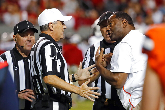 Syracuse coach Dino Babers protests a call with the referee during the second half of the team's NCAA college football game against North Carolina State in Raleigh, N.C., Thursday, Oct. 10, 2019. (AP Photo/Karl B DeBlaker)