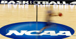 FILE - In this March 14, 2012, file photo, a player runs across the NCAA logo during practice in Pittsburgh before an NCAA tournament college basketball game. NCAA basketball administrators apologized to the women's basketball players and coaches after inequities between the men's and women's tournament went viral on social media. Administrators vowed to do better. NCAA Senior Vice President of Basketball Dan Gavitt spoke on a zoom call Friday, March 19, 2021, a day after photos showed the difference between the weight rooms at the two tournaments. (AP Photo/Keith Srakocic, File)
