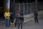 A group of Venezuelan political police officers, SEBIN, with their faces covered stand on guard at the main door of SEBIN headquarters in Caracas, Venezuela, Wednesday, May 16, 2018. In two short videos shot on a cell phone and posted Wednesday on his Facebook page U.S jailed citizen Joshua Holt said his life was threatened during a disturbance by inmates that include President Nicolas Maduro's top opponents. Venezuela's chief prosecutor sent a commission to the jail to discuss the prisoners' demands. (AP Photo/Fernando Llano)
