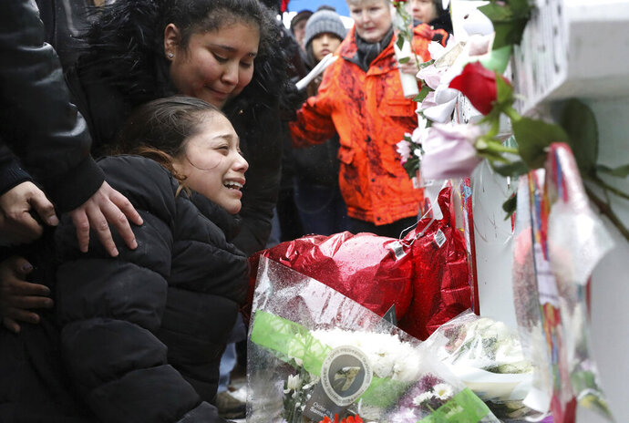 One of victim Vicente Juarez's daughter Diana Juarez cries at a makeshift memorial Sunday, Feb. 17, 2019, in Aurora, Ill., near Henry Pratt Co. manufacturing company where several were killed on Friday. Authorities say an initial background check five years ago failed to flag an out-of-state felony conviction that would have prevented a man from buying the gun he used in the mass shooting in Aurora. (AP Photo/Nam Y. Huh)