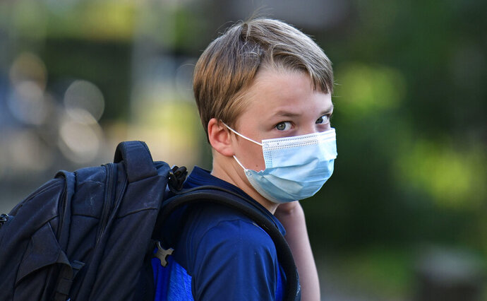 Pupil Moritz is on his way to the first day at his new school in Gelsenkirchen, Germany, Wednesday, Aug. 12, 2020. Students in North Rhine-Westphalia will have to wear face masks at all times due to the coronavirus pandemic as they return to school this Wednesday. (AP Photo/Martin Meissner)