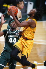 Oakland's Rashad Williams, right, puts up a shot and draws a foul against Michigan State's Gabe Brown (44) during the first half of an NCAA college basketball game, Sunday, Dec. 13, 2020, in East Lansing, Mich. (AP Photo/Al Goldis)
