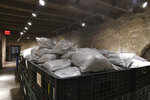 Bags of soil, cataloged and labeled, are placed in a bin in the Long Barrack on the Alamo grounds during an archaeological survey on Tuesday, Aug. 13, 2019.  (Billy Calzada/The San Antonio Express-News via AP)