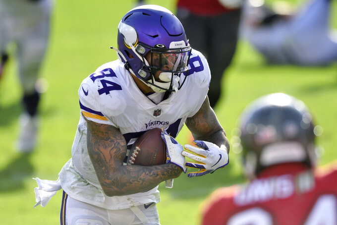 Minnesota Vikings tight end Irv Smith Jr. (84) scores on a 14-yard touchdown pass from quarterback Kirk Cousins during the second half of an NFL football game against the Tampa Bay Buccaneers Sunday, Dec. 13, 2020, in Tampa, Fla. (AP Photo/Jason Behnken)
