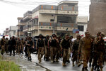 Pakistan army soldiers leave after the crackdown operation against terrorists in Peshawar, Pakistan, Tuesday, April 16, 2019. Pakistani authorities say a raid by security forces on a militant hideout in the northwestern city of Peshawar triggered a 15-hour shootout in which a police officer and many suspected militants were killed. (AP Photo/Muhammad Sajjad)