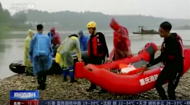 This June 22, 2020, image made from China's CCTV video shows rescue workers searching on the river banks in southwestern China's Chongqing province. Eight children drowned in a river in southwestern China after one fell in and the others jumped in to help, state media said Monday. (CCTV via AP)